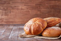 Свежий горячий хлеб в linen полотенце на коричневом деревянном столе Открытый космос для записи текста меню рекламировать стоковое фото