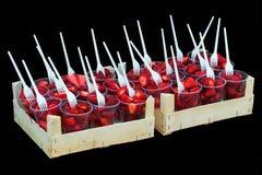 Свежий готов-к-съешьте клубники в пластичных чашках, изолированных на черной предпосылке Стоковое Фото