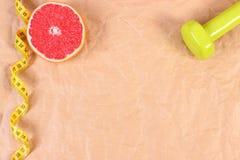 Свежий грейпфрут, рулетка и гантели для фитнеса, здоровой концепции образов жизни Стоковые Фото