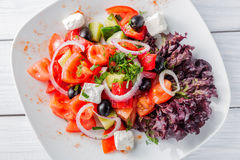 Свежий греческий салат с луком на белых плите и деревянном столе Взгляд сверху Стоковое фото RF