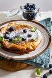 Свежий домодельный голландский блинчик младенца с голубиками и мятой на деревенской предпосылке белья Завтрак, ресторан, концепци стоковые фотографии rf