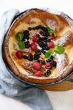 Свежий домодельный голландский блинчик младенца с напудренным сахаром, свежие ягоды и мята на завтрак со стеклом молока стоковое фото