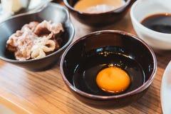 Свежий желток и белое яйцо в керамическом шаре для окунать с кипеть говядиной Shabu стоковая фотография