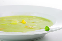 Свежий зеленый горох на краю белой плиты с овощным супом Стоковое фото RF