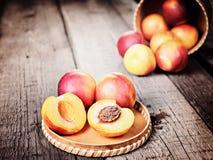 Свежий зрелый плодоовощ персика нектарина, подрезывает деревенскую предпосылку Стоковое фото RF