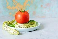 Свежий зрелый томат на серой предпосылке Лента для измеряя тома тела пригодность диетпитания стоковое фото rf