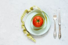 Свежий зрелый томат на серой предпосылке Лента для измеряя тома тела пригодность диетпитания стоковая фотография