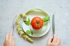 Свежий зрелый томат на серой предпосылке Лента для измеряя тома тела пригодность диетпитания стоковое изображение