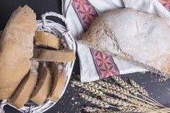 Свежий испеченный хлеб на таблице с ушами пшеницы Свеже испеченные хлеб и плюшки в хлебопекарне на черной предпосылке отрезанный  Стоковое Изображение RF