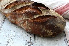 Свежий и покрытый коркой хлеб на деревенской таблице Стоковые Изображения
