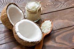 Свежий кокос треснул в половине на деревянном столе с обломоками кокоса в стеклянном опарнике и в деревянной ложке с местом для стоковые фотографии rf