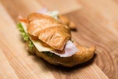 Свежий круассан с ветчиной и сыром на деревянной доске Стоковое Фото