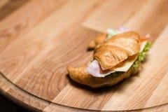 Свежий круассан с ветчиной и сыром на деревянной доске Стоковая Фотография RF