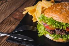 Свежий крупный план фраев бургера и француза на деревянном столе стоковая фотография