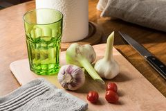 Свежий молодой чеснок, нож, небольшие томаты и зеленое стекло воды на кухонном столе стоковая фотография rf