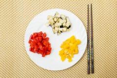 Свежий отрезанный красные и желтые сладостный перец и баклажан на белой плите Китайский и японский образ жизни еда принципиальной Стоковое Изображение RF