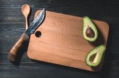 Свежий отрезок авокадоа в 2 половины с косточкой на декоративной разделочной доске Стоковое Фото