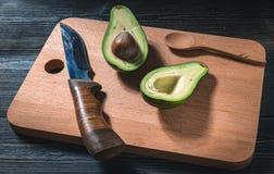 Свежий отрезок авокадоа в 2 половины с косточкой на декоративной разделочной доске Стоковые Фото