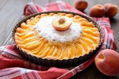 Свежий пирог персика взбрызнутый с сахаром на деревянной предпосылке Стоковое Фото