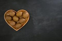 Свежий плодоовощ кивиа в сердце сформировал деревянную плиту Стоковые Фотографии RF