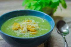 Свежий помятый суп с брокколи и зелеными фасолями в голубой плите на деревянной предпосылке стоковое изображение