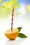 Свежий половинный апельсин с выпивая соломой на белой предпосылке Стоковое Изображение RF
