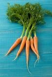Свежий пук морковей на голубой деревянной предпосылке Стоковая Фотография RF