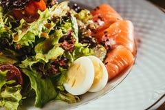 Свежий салат с овощами, яичками и семгами служил на белой плите Стоковые Изображения
