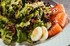 Свежий салат с овощами, яичками и семгами служил на белой плите Стоковое Изображение RF