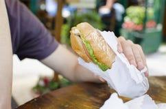 Свежий сандвич в руке ` s человека Стоковые Изображения