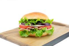 Свежий сандвич с овощами и ветчиной на деревянной доске Стоковые Изображения RF