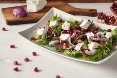 Свежий салат весны с сыром фета, красным луком и семенами гранатового дерева в белом блюде на деревянной предпосылке Стоковые Изображения