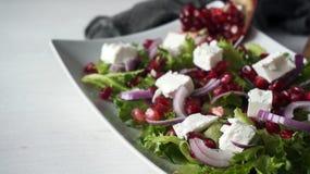 Свежий салат весны с сыром фета, красным луком и семенами гранатового дерева в белом блюде на деревянной предпосылке Стоковые Изображения RF