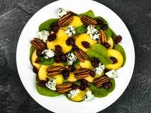 Свежий салат персика и шпината с гайками пекана и голубым сыром Стоковые Изображения