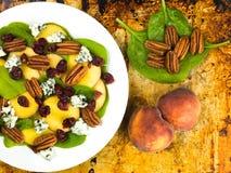 Свежий салат персика и шпината с гайками пекана и голубым сыром Стоковая Фотография RF