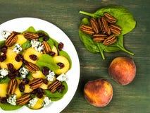 Свежий салат персика и шпината с гайками пекана и голубым сыром Стоковое Изображение