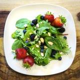 Свежий салат с смешанными зелеными цветами, ягодами, и гайками Стоковое Изображение RF