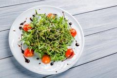 Свежий салат томатов вишни, салат, beniseed и соус на белой плите и белом деревянном столе Стоковые Изображения RF