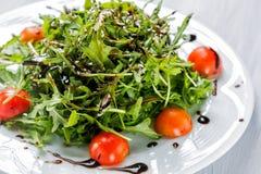Свежий салат томатов вишни, салат, beniseed и соус на белом конце плиты вверх Стоковое Изображение RF