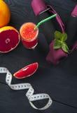 Свежий сок грейпфрута, измеряя лента и гантели Стоковая Фотография RF
