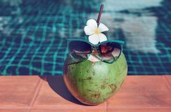 Свежий сок кокоса с соломой, цветком и солнечными очками на границе стоковые изображения