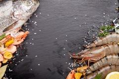 Свежий сырцовый продукт моря с специями на черном камне Стоковые Изображения RF