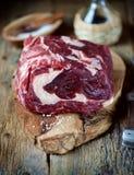 Свежий сырцовый стейк говядины с солью моря на доске сервировки на старой деревянной предпосылке Стоковое Фото