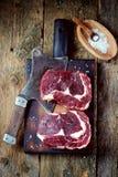 Свежий сырцовый стейк говядины с солью моря на доске сервировки на старой деревянной предпосылке Стоковые Фотографии RF