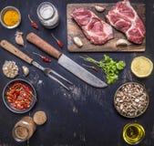 Свежий сырцовый стейк свинины на разделочной доске с ножом и вилка для мяса с горячими красными перцами, масла лимона на деревянн Стоковые Изображения RF
