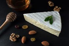 Свежий сыр бри на черной каменной доске с гайками, медом и травами стоковые изображения rf