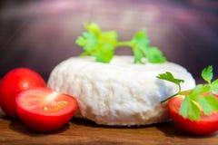 Свежий сыр с превосходными вкусом и ароматностью Сыр на деревянной разделочной доске с томатами и свежими травами стоковая фотография rf