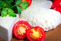Свежий сыр с превосходными вкусом и ароматностью Сыр на деревянной разделочной доске с томатами и свежими травами стоковое изображение rf