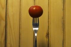 Свежий томат на вилке вставил в деревянной предпосылке Стоковое Изображение