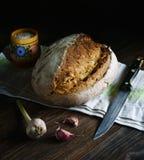 Свежий хлеб пшеницы, чеснок, деревянный шейкер соли с солью, полотенце хлопка, нож Весь это лежит на темном деревянном столе Smel стоковые фото